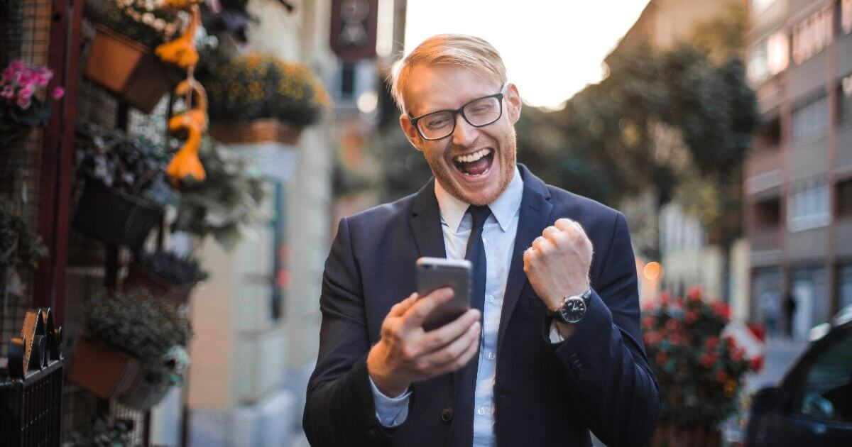 blond man using mobile phone